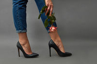 Beautiful female legs in black shoes with heels and jeans, a woman's hand with a tattoo is holding a pink rose on a dark background with space for text. Stylish layout for your ideas