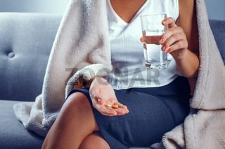 Close view on woman sitting on the sofa holding drugs