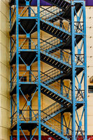 Tall fire escape made of metal. A tall metal fire escape against a modern building wall