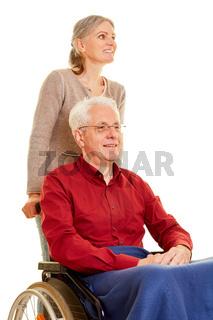 Frau betreut Mann im Rollstuhl
