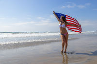 A Lovely Patriotic Brunette Model Poses On The Coast With An American Flag