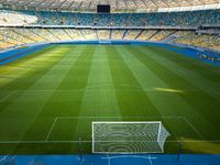 KIEV, UKRAINE - July 19, 2018: Panoramic view of a green field with blue-yellow stands and a football goal of the Olympic National Sports Complex