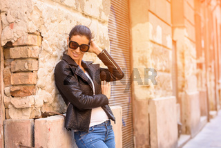Fashion Portrait of a cheerful young woman in a european urban neighbourhood