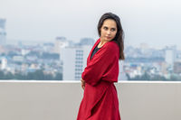 Outdoor portrait of young beautiful woman dancing on the rooftop with city view at rainy moody day