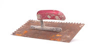 Rusty old notched trowel on white