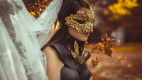 Golden, mysterious woman dressed in white with mask of leaves in copper and gold color in a garden in autumn