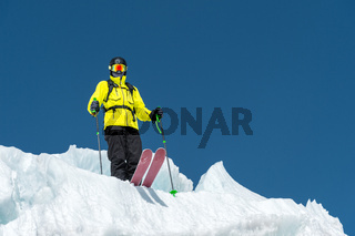 A freerider skier in complete outfit stands on a glacier in the North Caucasus. Skier preparing before jumping from the glacier