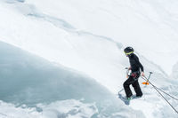 A professional mountaineer in a helmet and ski mask on insurance makes a nick-hole in the glacier against the backdrop of the Caucasian snow-capped mountains