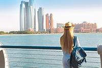 Traveler woman looking at Emirates Palace and skyscrapers of Abu Dhabi