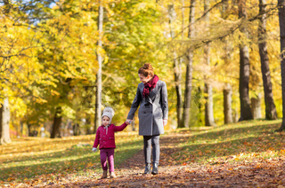 happy mother and little daughter at autumn park