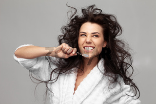 brunette woman brushes her teeth