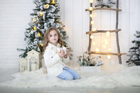 Little girl unpacking christmas gift at Christmas decoration