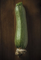 Photo of a courgette on a wooden table with black vignette border, still life