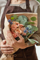 Florist in a brown apron with a bouquet of coral roses. Girl is holding a flowers in her hands. Close-up view. The gift to Mother's Day.