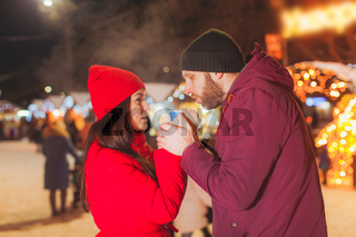 Cheerful couple drinking hot wine from one cup at Christmas fair