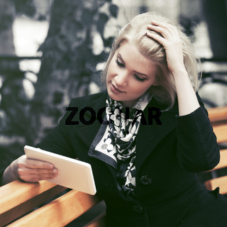 Young fashion blond business woman using digital tablet computer in city street