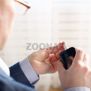 Mid age Man doing blood test with personal glucometer
