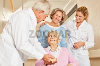 Arzt in Reha Klinik hält die Hand einer Seniorin