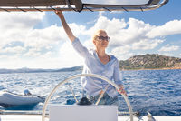 Attractive blond female skipper navigating the fancy catamaran sailboat on sunny summer day on calm blue sea water.