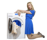 young woman in a blue dress kneeling unloads laundry from a new washing machine