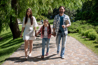 happy young family spending time in park on summer day