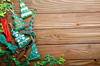 Handmade rustic green felt Christmas tree decorations and scissors flat lying on wooden table