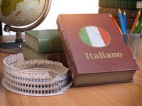 Studying and learn Italian concept. Book with flag of Italy and Coliseum on the table.