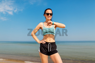 happy woman with fitness tracker on summer beach