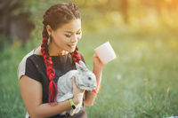 Pretty Girl With Hair Braiding Huggs a Rabbit on Beautiful Summer Nature