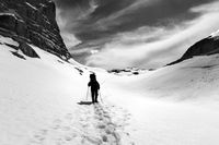 Black and white silhouette of hiker on snowy plateau