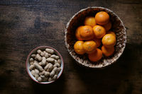 bowls of peanuts and clementines on rustic table