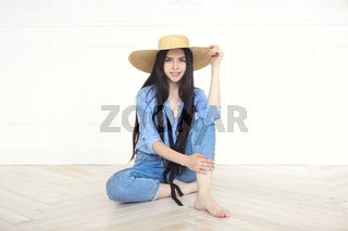 Beautiful woman in straw hat and blue shirt looking at camera