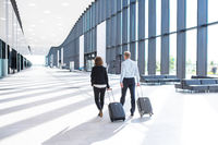 Business people walking with wheeled bags