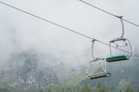 A chairlift with mountains and fog in the background