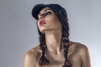 Dark fashion studio portrait of young woman in baseball cap