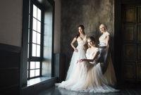 Three women near window wearing wedding dresses