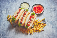 Assortment of three tasety hot dogs, placed on wooden cutting board