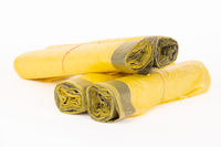 Rolls of yellow trash bags on white background