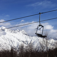 Chair lift in snowy mountains at nice day