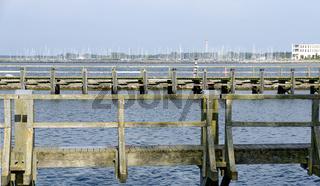 Hölzerne Stege im Hafen von Warnemünde an der Ostsee mit Segelboothafen im Hintergrund