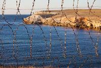 Old rusted barbed wire and sea coast