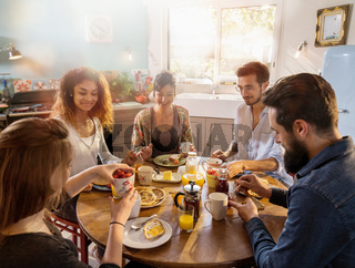 bunch of multi-ethnic friends gathered around a table for breakf
