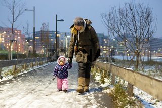 Mother and daughter walking in a snowy park in the winter time.