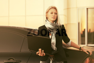 Young fashion business woman using laptop next to her car