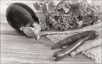 Green salad, eggplant and chili on a wooden table, black and white image.