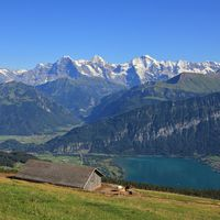 Snow capped mountains Eiger, Monch and Jungfrau, view from Mount Niederhorn. Azure blue Lake Thun, Bernese Oberland, Switzerland.