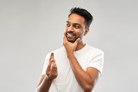 smiling indian man applying grooming oil to beard