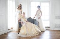 Young women near window wearing wedding dresses
