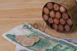 Luxury Cuban cigars and money on the wooden desk