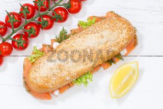 Sandwich Baguette Vollkorn Brötchen belegt mit Lachs Fisch von oben auf Holzbrett